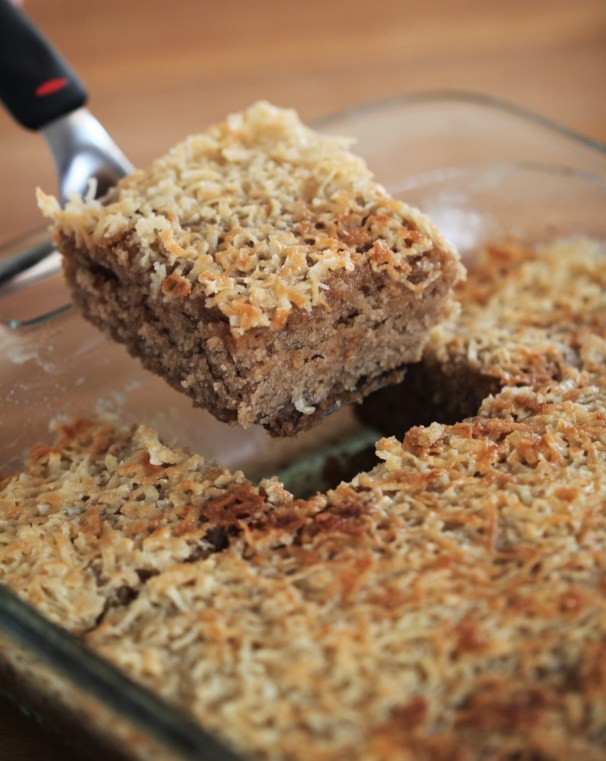 A spatula lifts a slice of oatmeal cake with coconut frosting out of a baking dish, which contains the rest of the cake. The cake is cut into squares.