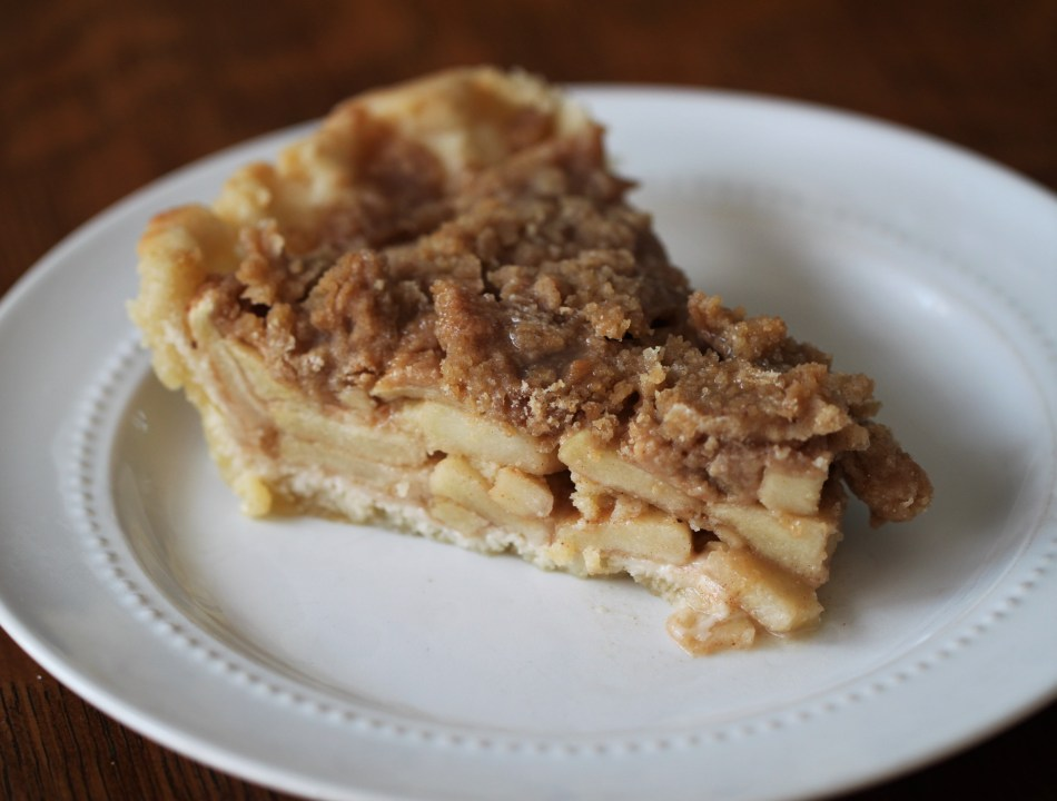 A slice of crumble top apple pie sits on a white plate. The pie features a pale crimped crust; several layers of stacked apples are visible in the cross-section.
