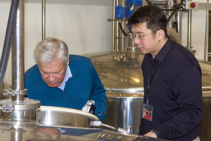 Dr. Jim Swan (L) and King Car Master Blender Ian Chang examine a fermenter in this file photo from March 29, 2011. Photo ©2011 by Mark Gillespie.