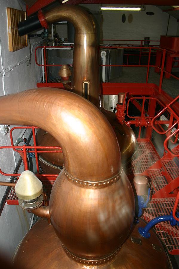 """Zwei kupferne Brennblasen in der Edradour-Destillerie. """"002 Edradour Kessel 2048x3072"""" von Edradour 07:09, 9 September 2007 (UTC) - Eigenes Werk. Lizenziert unter CC BY-SA 3.0 über Wikimedia Commons."""