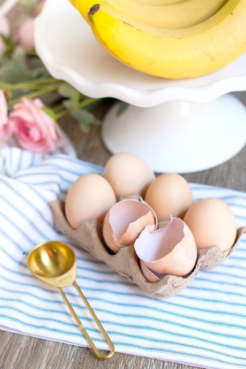 Cake stand with bananas on top while a 6 count of brown eggs are shown on a striped napkin.