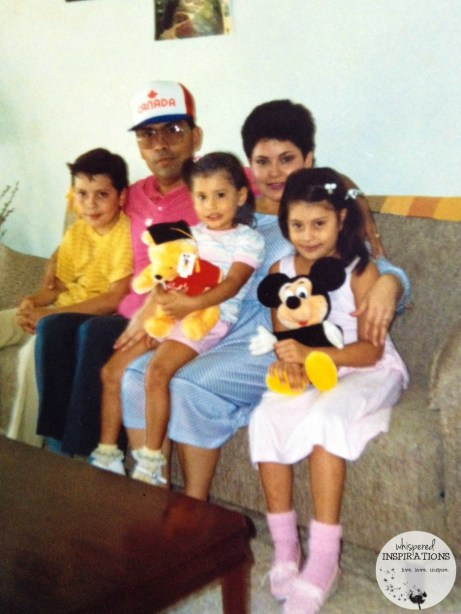 A young couple pose with their three children.