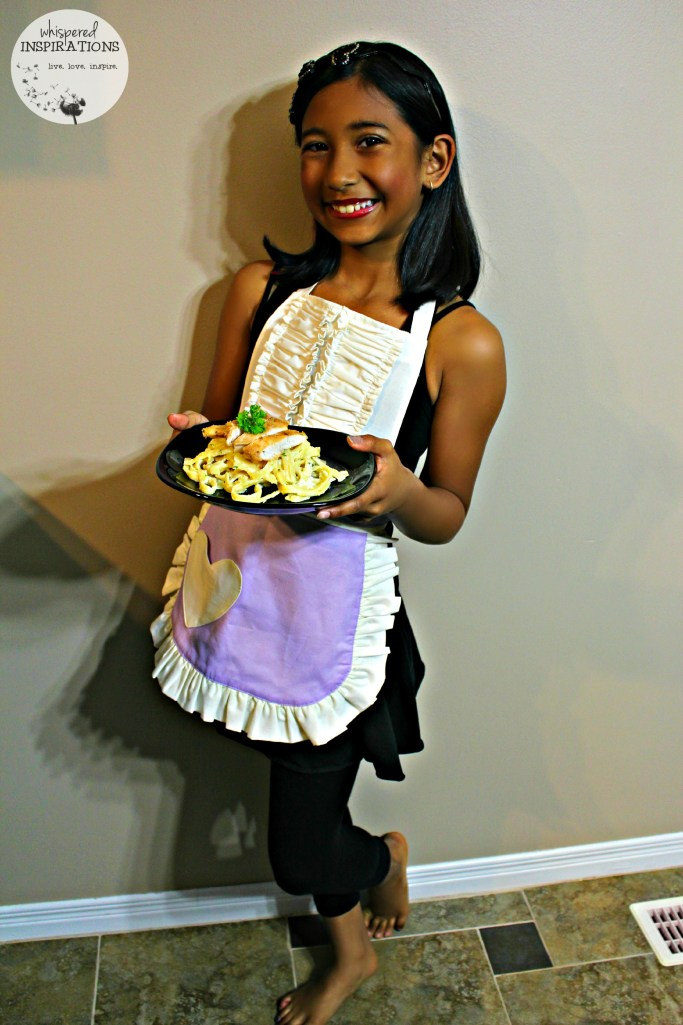 A little girl wears a Sugar Apron while holding the plate of pasta she just made.