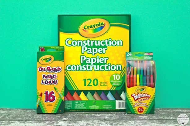 A pad of Crayola construction paper and pencil crayons are displayed.