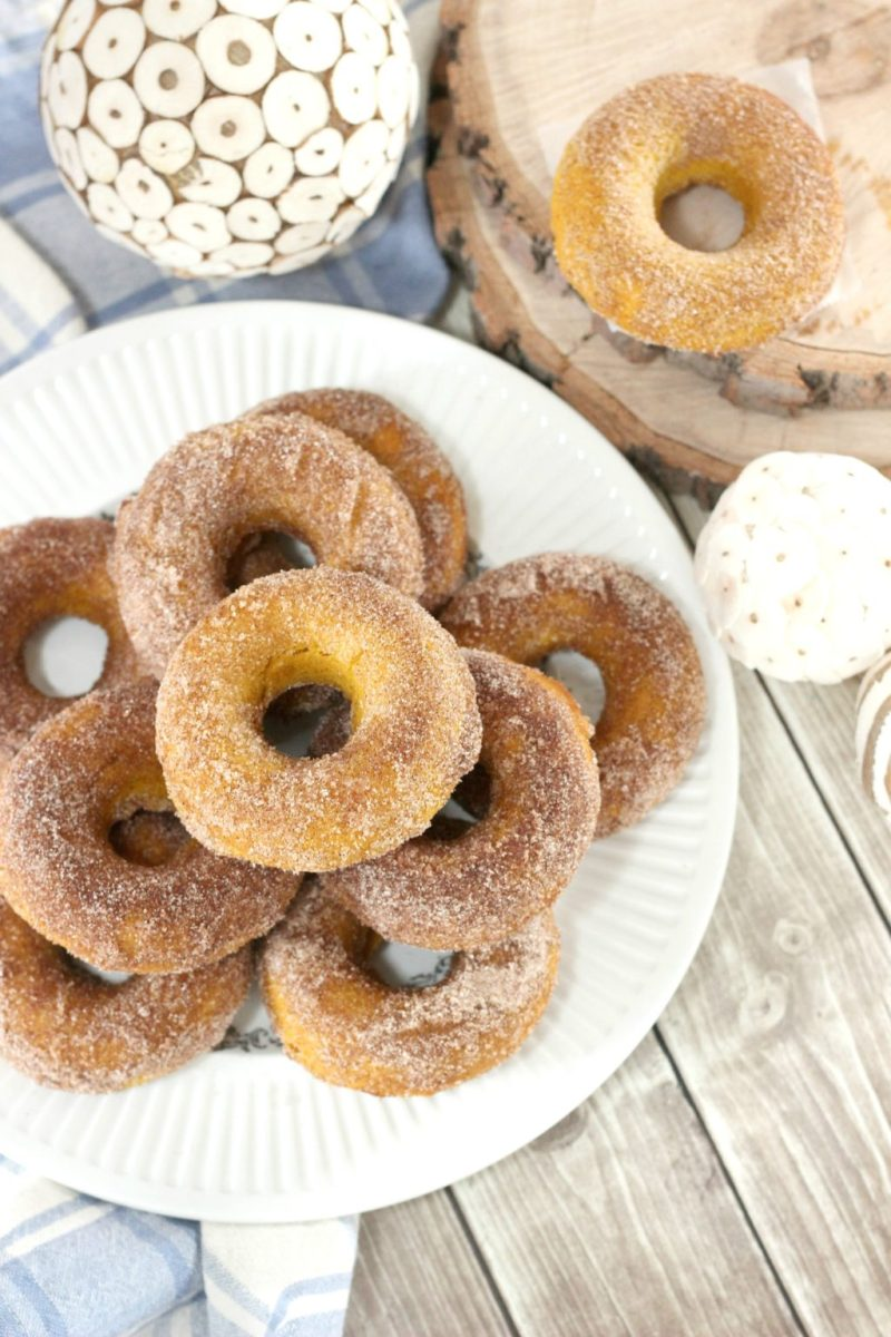 A plate is fully stacked with sugar coated baked pumpkin spice donuts, surrounded by fall decor.