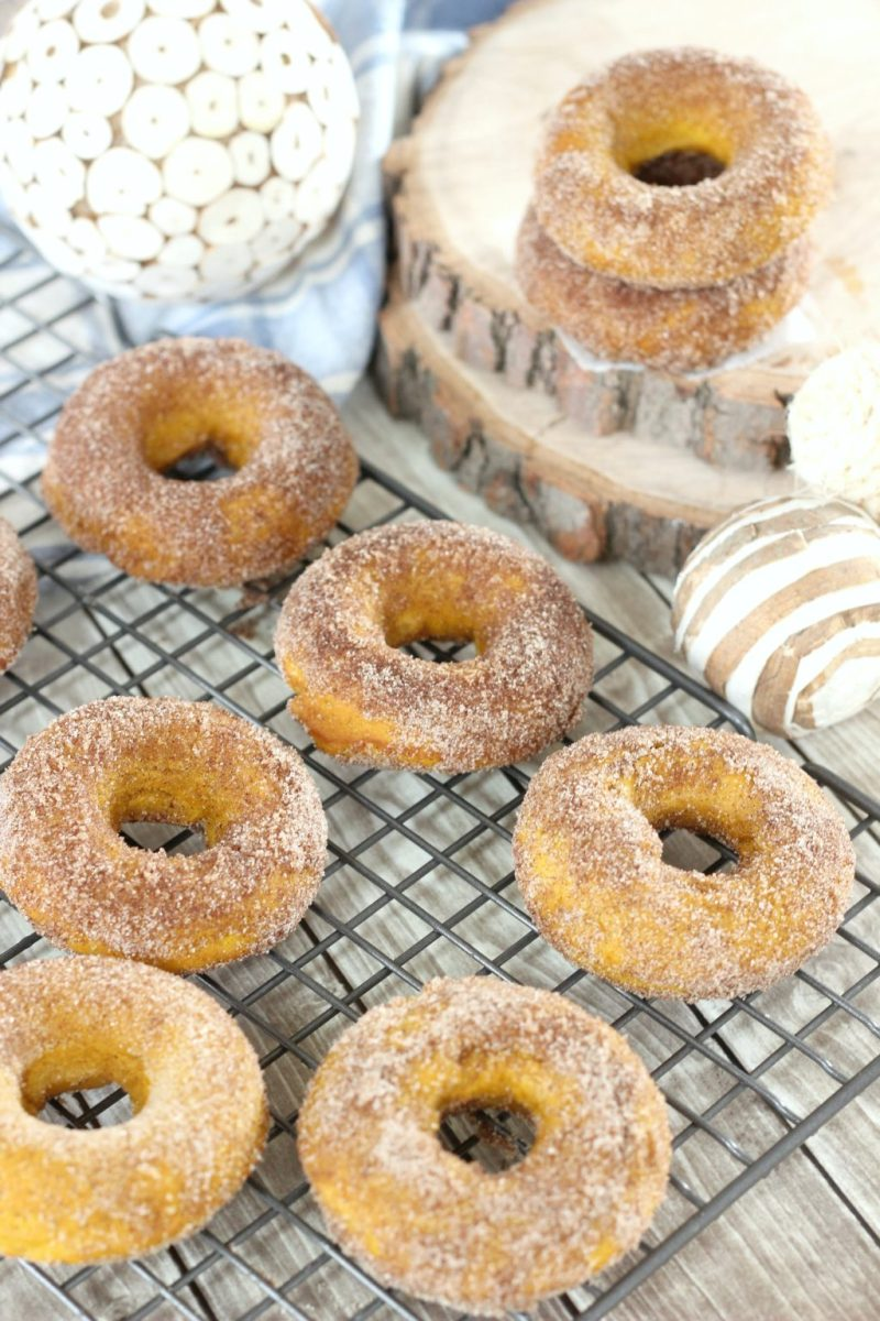 Baked pumpkin spice donuts are shown on a cooling rack with fall decor surrounding them.