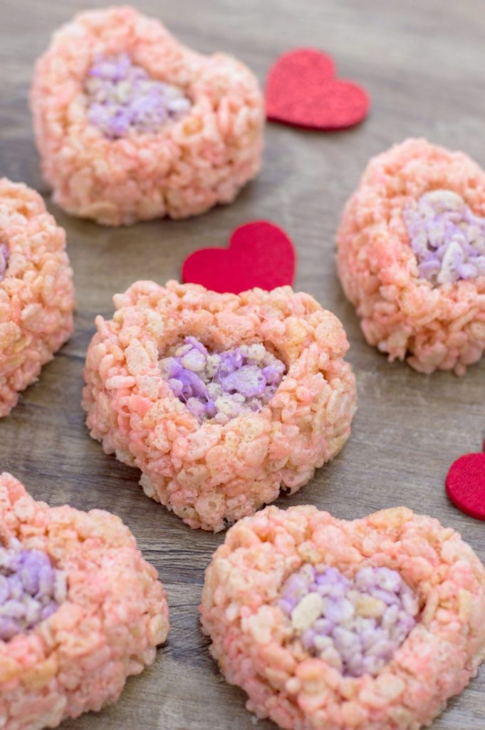 The finished Valentine's Day Rice Krispies treats on a wooden background with felt hearts to decorate.