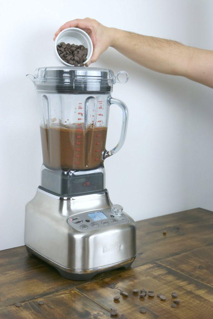 A hands adds dark chocolate to hazelnut butter mixture.