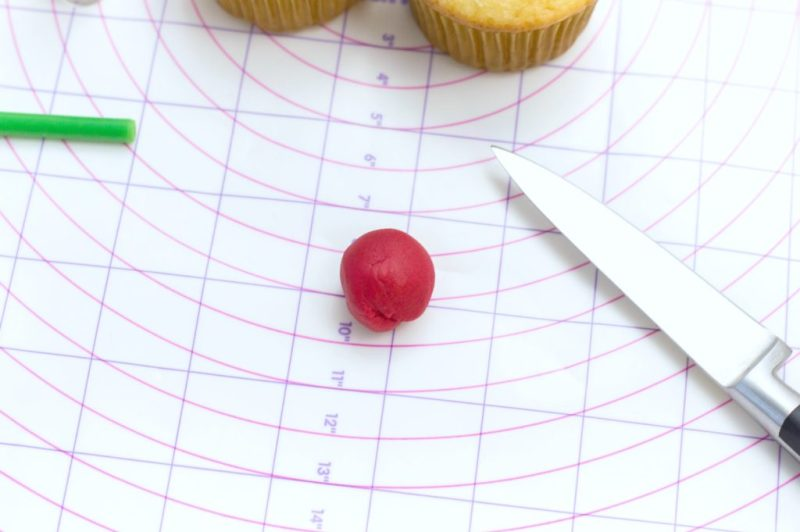 Red fondant ball on a Wilton measuring chart, knife, cupcakes, and brush is pictured.