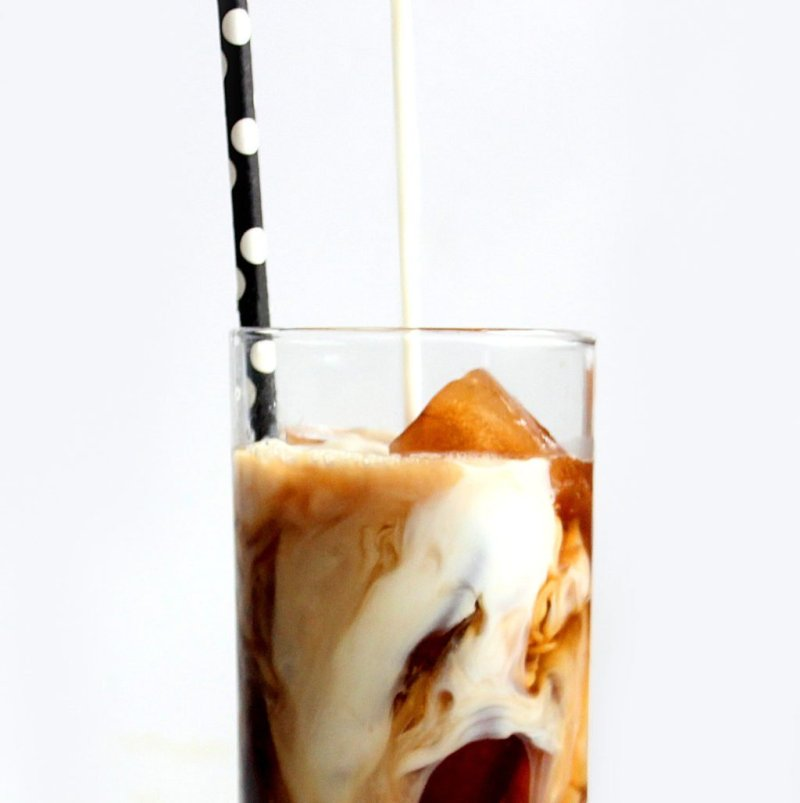 Milk being poured into iced coffee in a clear glass with a polka dot straw.