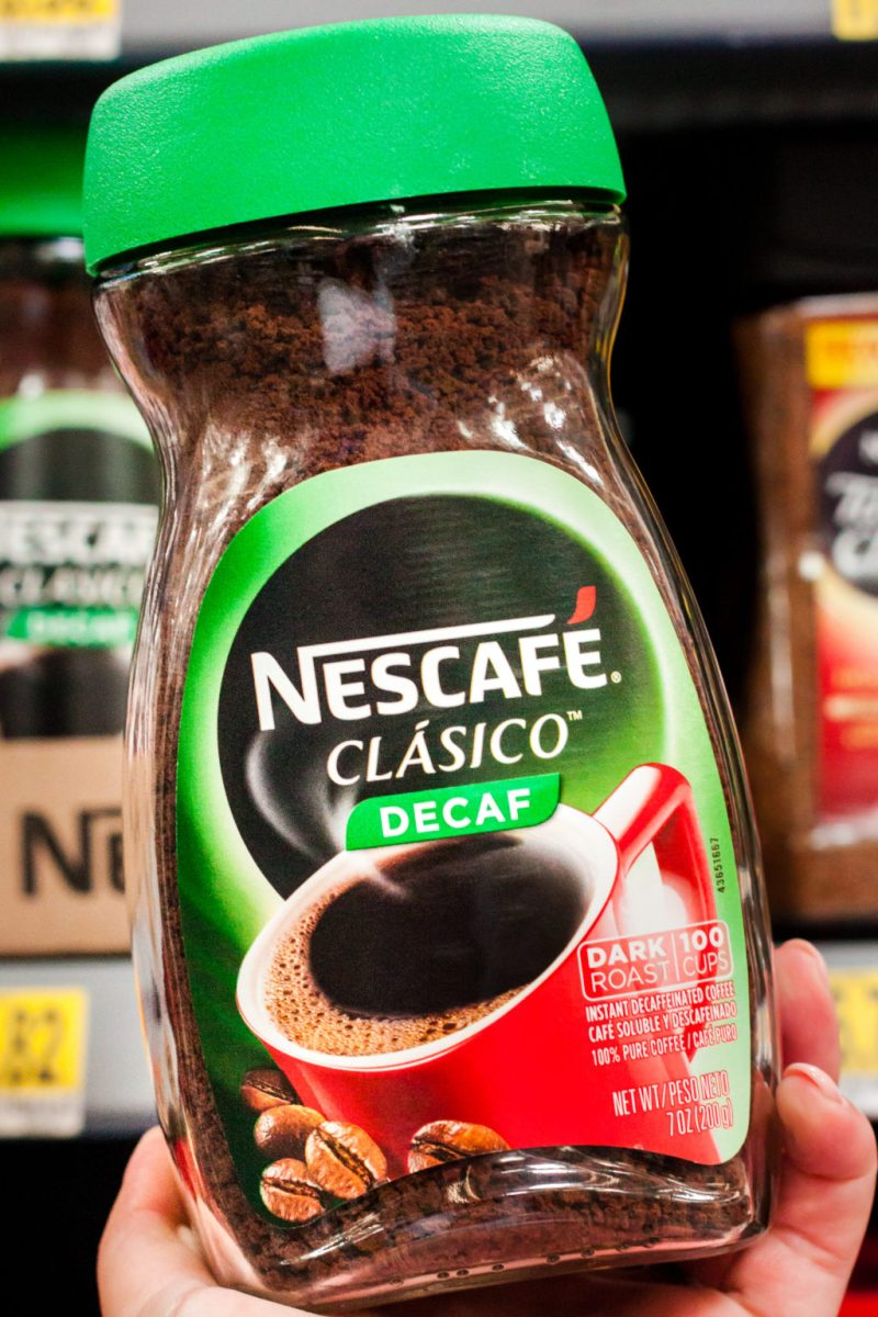 Holding NESCAFE CLASICO in the coffee aisle.