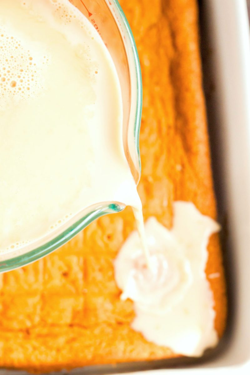 Cream is being poured onto the cake.