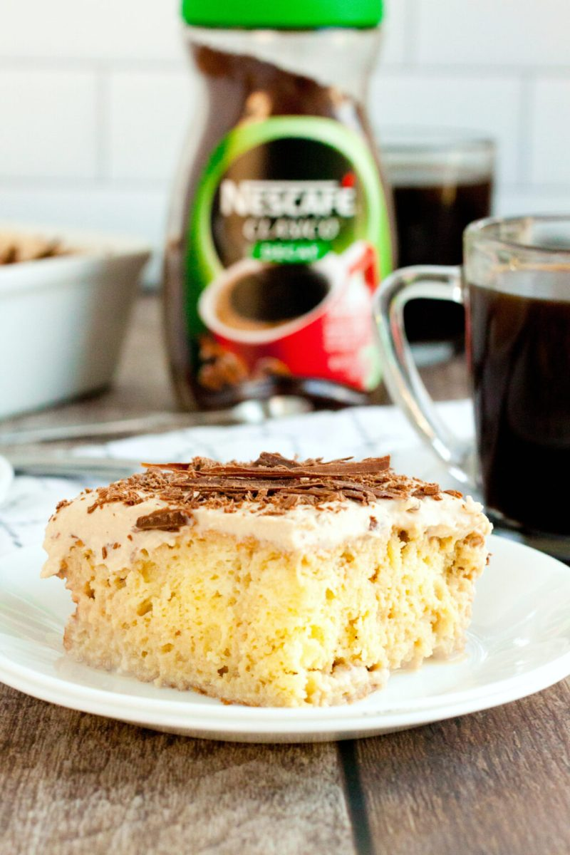 A plate with a piece of Coffee Tres Leches Cake with the Nescafe Clasico Decaf in the background.