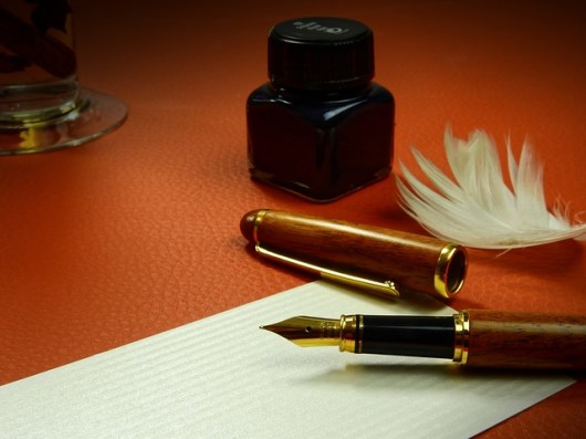 Image of a fountain pen and feather indicating traditional values with inspiration from the spirit world when responding to our contact form submissions