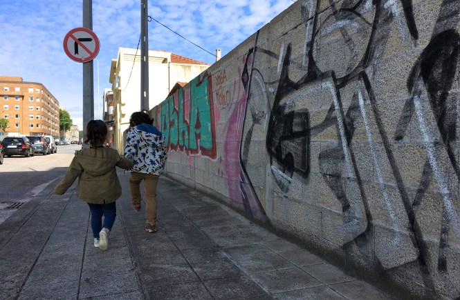 Brother and Sister walking past graffiti wall holding hands