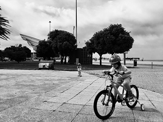 Ridding his big bicycle - black & white