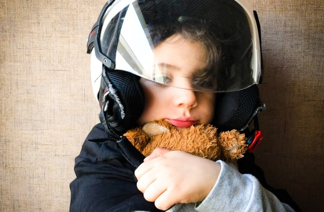 kid with wearing a motorbike helmet and cuddling his teddy