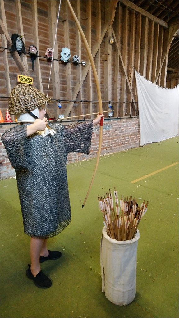 Child dressed in chainmail shooting a medieval longbow
