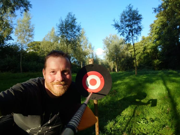 Man smiling with arrow in target