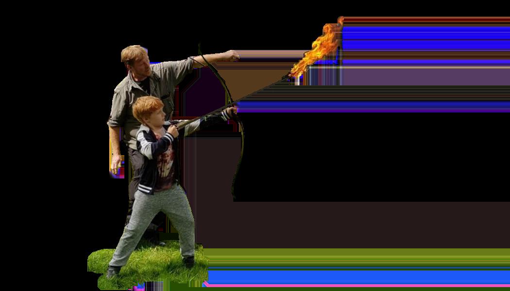 Man coaching boy to shoot a flaming arrow