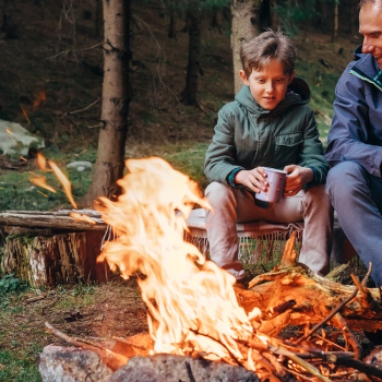 Parent and child sitting by campfire