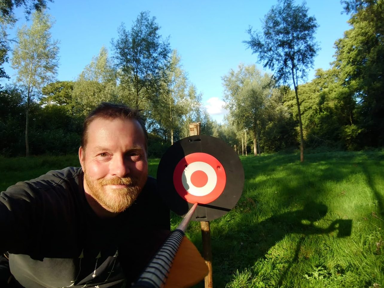 Man smiling with an arrow in a very small target