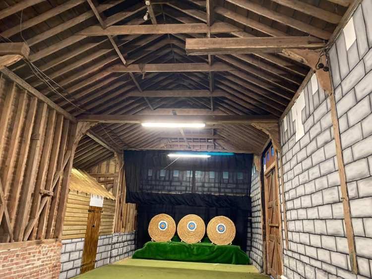 Indoor archery range themed to look like a castle courtyard
