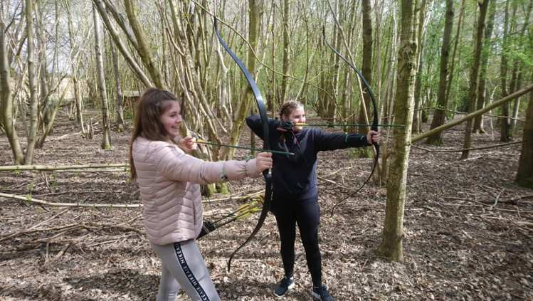 Two teenage girls shooting bows and arrows on a beginner's archery course