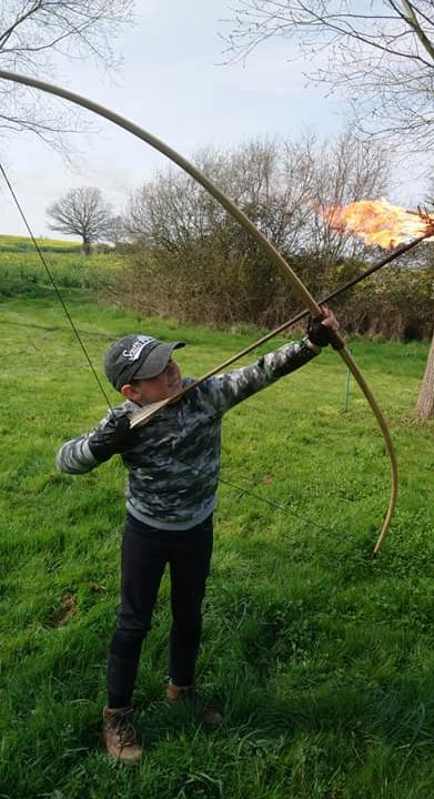 Young boy shooting a flaming arrow with help from coaches