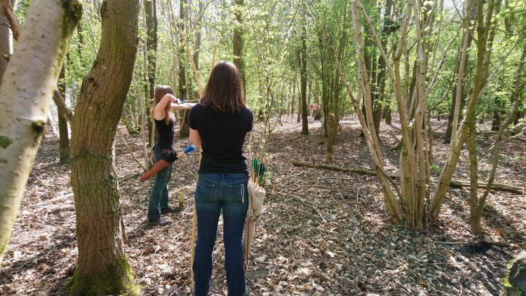 Women shooting together in woodland archery range