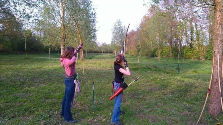 Two ladies learning longbow archery together on a beginner's archery course