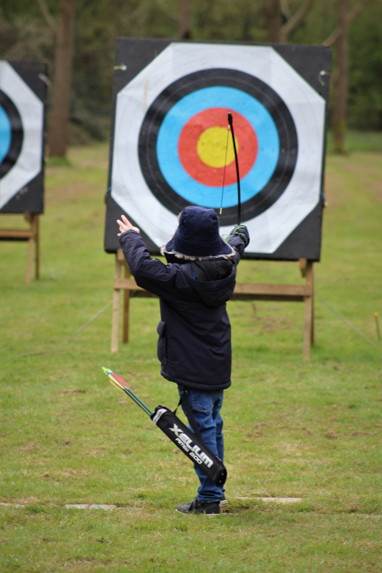 Little boy shooting an archery target with a recurve bow