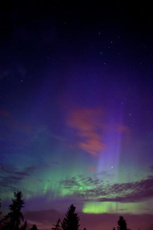 pre-dawn auroral storm. blue hues likely fromsun striking top of aurora