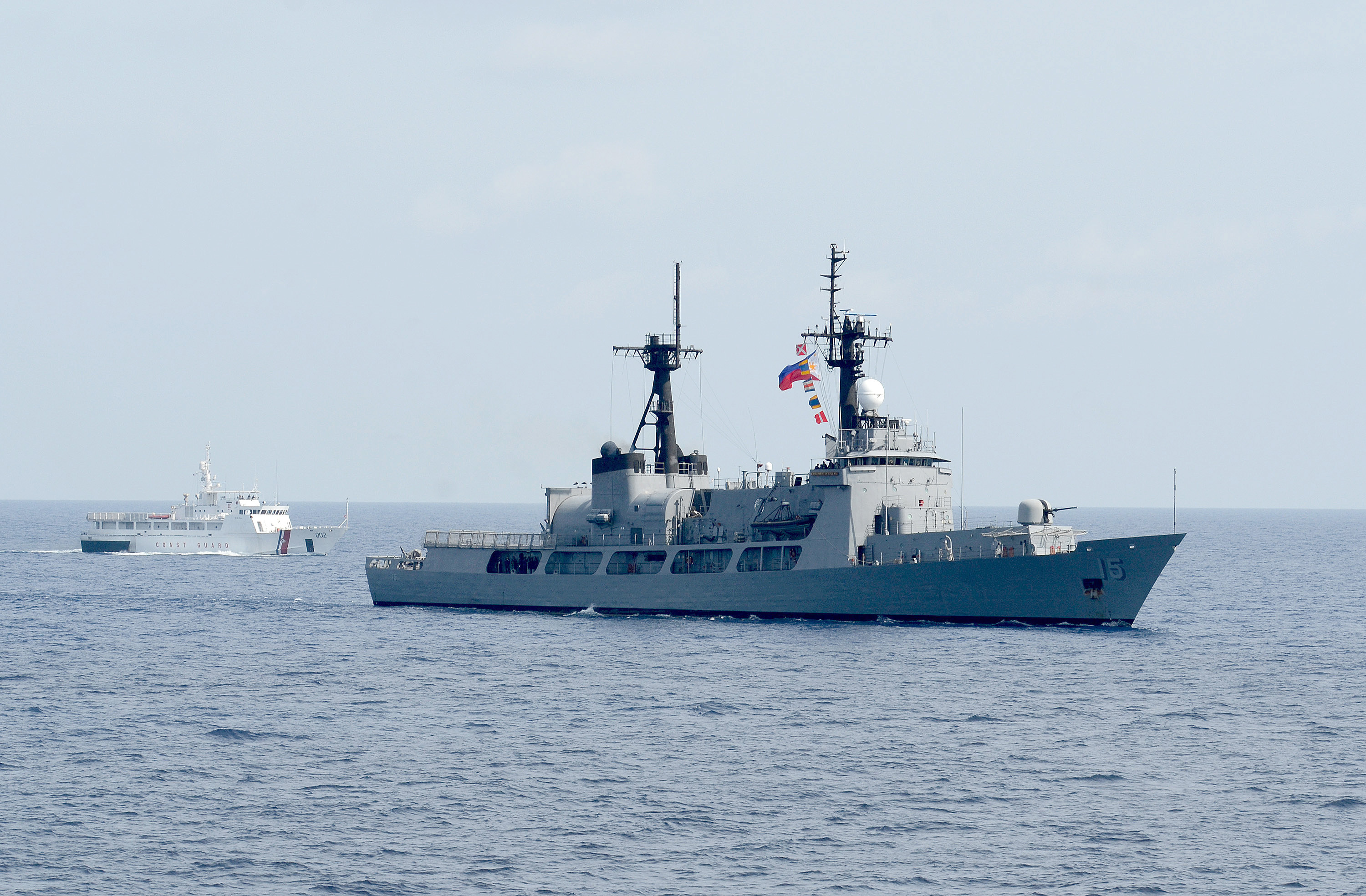 The Philippine frigate Gregorio del Pilar transits with a US Coast Guard vessel in the background.
