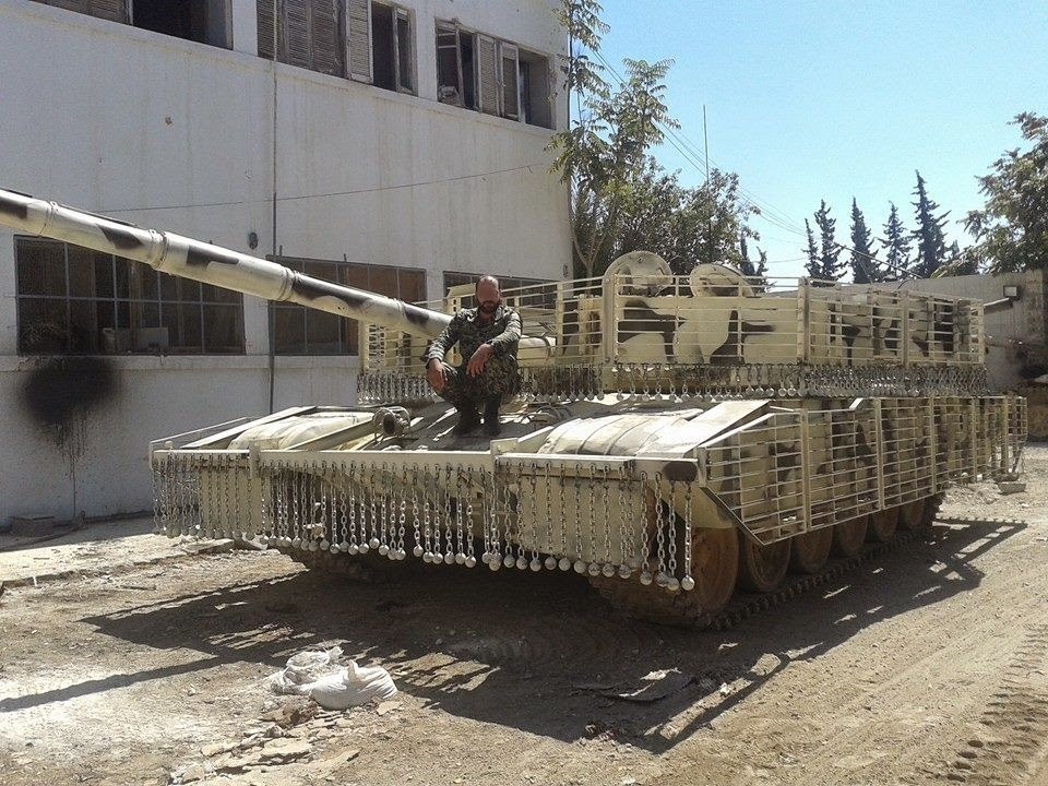 A Syrian Arab Army T-72 tank with added slat armor and ball-and-chain armor designed to disrupt anti-tank rockets and missiles prior to impact.