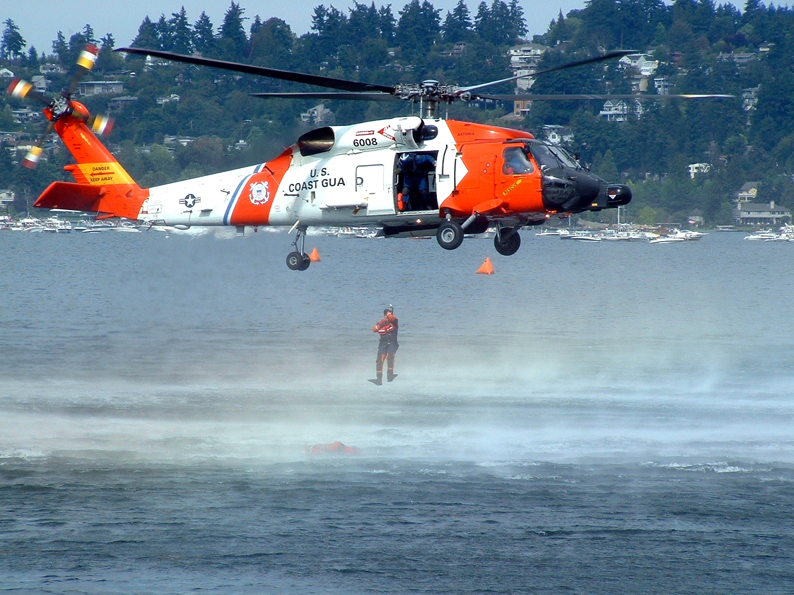 A Coast Guard HH-60J Jayhawk deploys a swimmer. Helicopters are often the preferred platform for conducting rapid rescue operations because of their ability to hover and retrieve casualties.