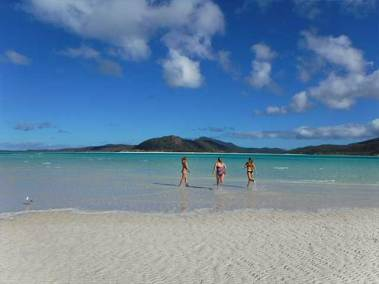 3 girls running into the water of a beach in the whitsunday islands