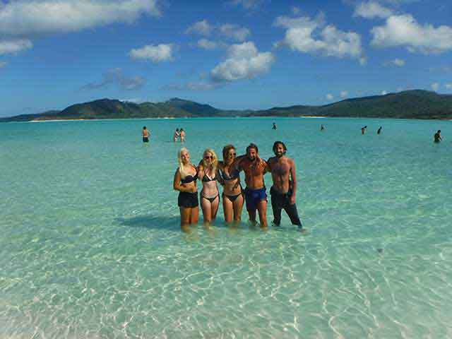 4 friends standing in clear waters of Whitehaven Beach