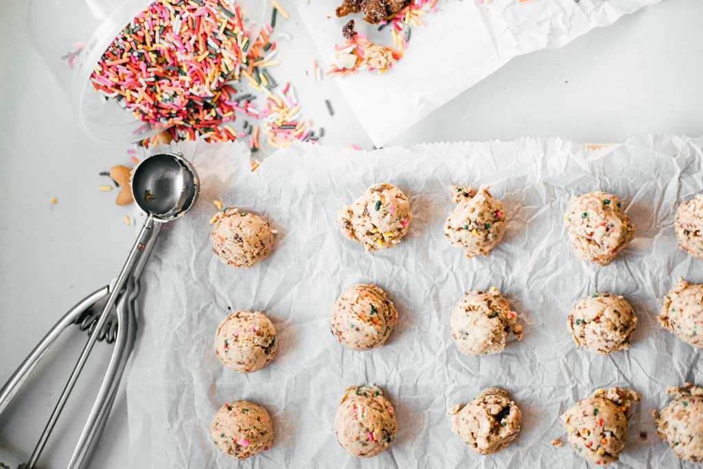 homemade cookie dough protein balls on parchment paper with a cookie scoop