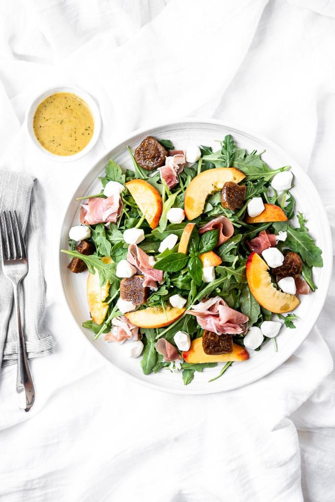 bowl of peach proscuitto salad with mozzarella