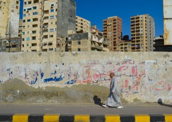 Egyptian man walking along the Alexandria Corniche.