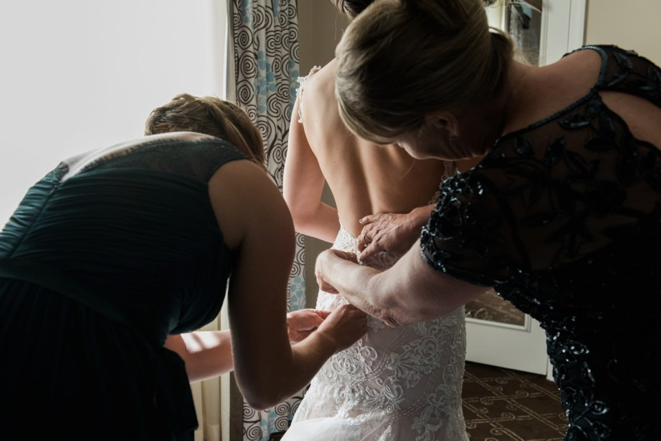 Bride getting dressed with the help of her mom and sister at the Palmer House in Chicago IL