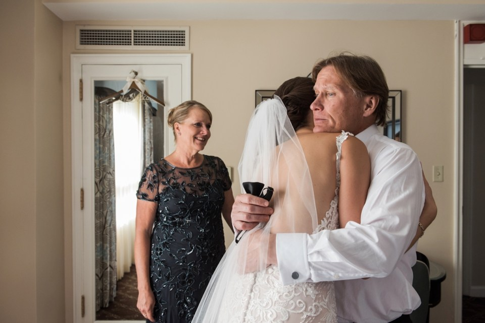 Dad giving his daughter a big hug after seeing her in her wedding dress