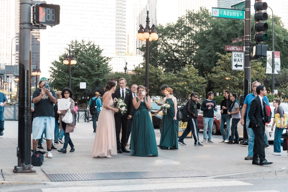 Wedding party takes photos of the couple on their phones as they cross the street in Chicago IL