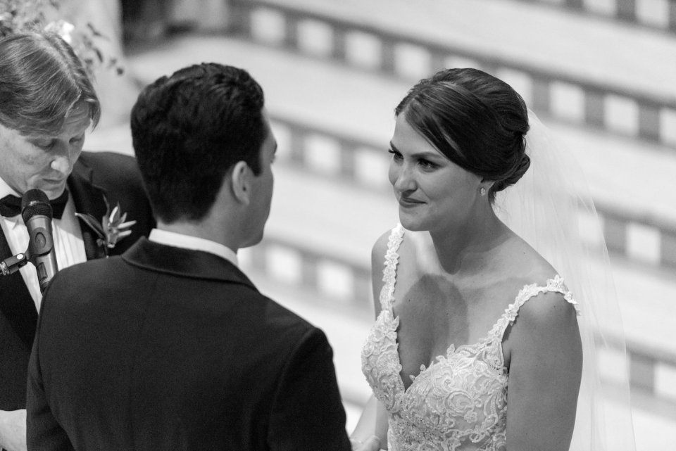 Bride smiles at the groom during their wedding ceremony