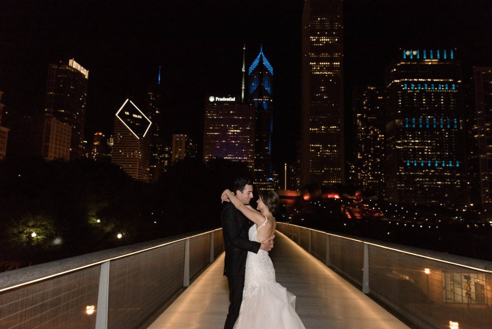 Couple snuggles close together during night time portraits with the Chicago skyline in the background