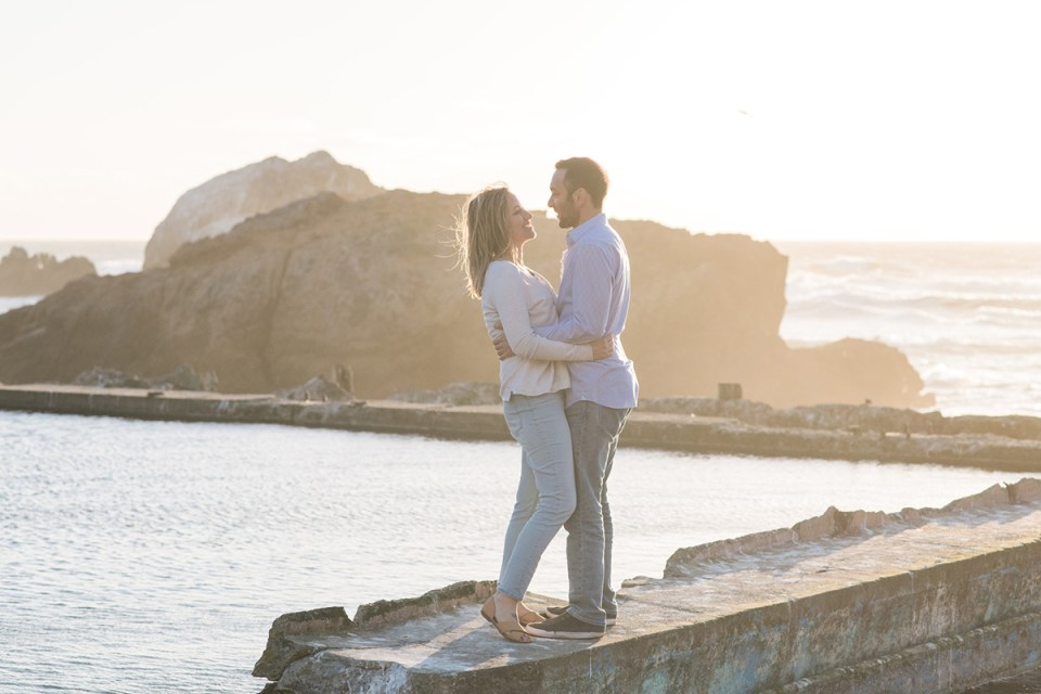 Couple smiling at each other on a windy day at Sutro Baths in San Franscico