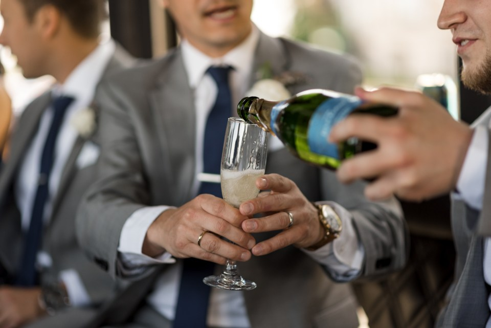 Best man pours champagne on a party bus for a toast