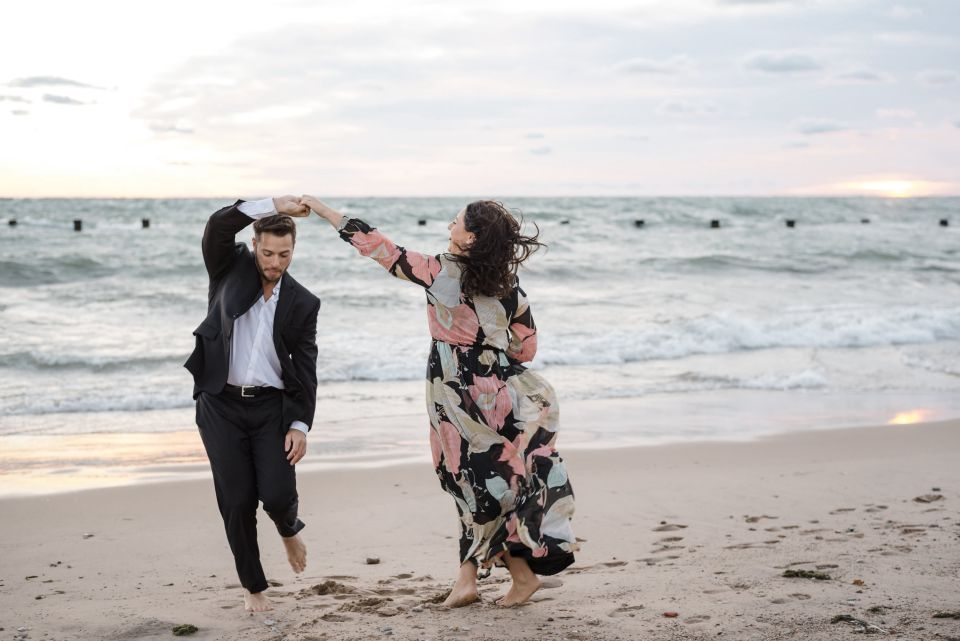Couple laughing and dancing on North Avenue Beach at sunrise