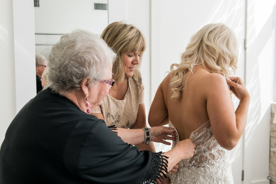 Bride's mother and grandmother help her get into her dress